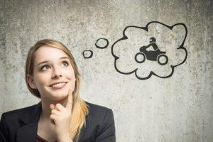 Junge Frau denkt an Motorrad
